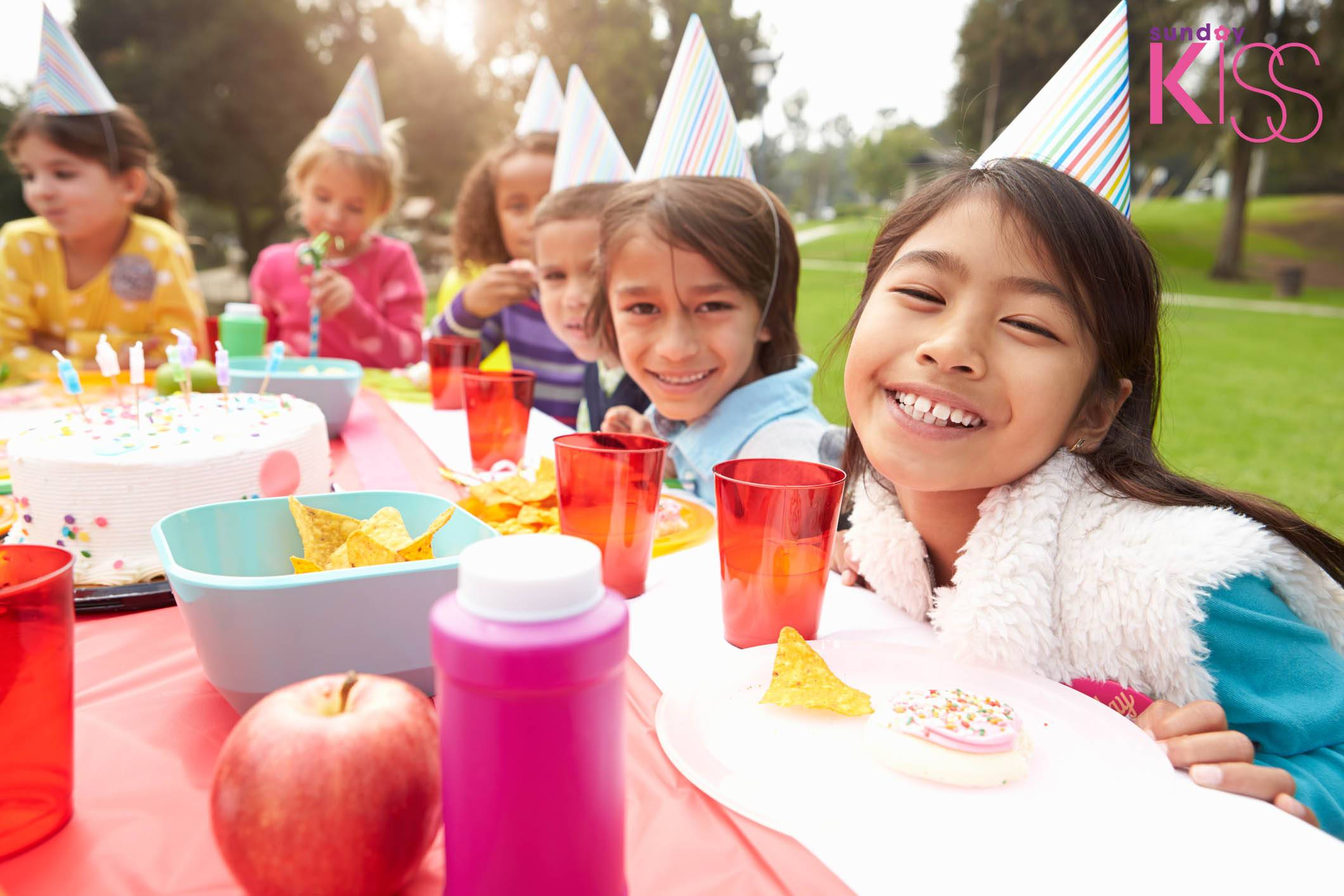 Group Of Children Having Outdoor Birthday Party Smiling Waering Party Hats