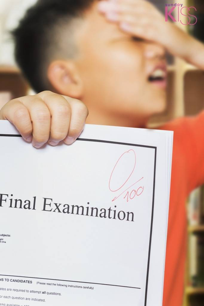 Young asian boy with Zero score on examination paper