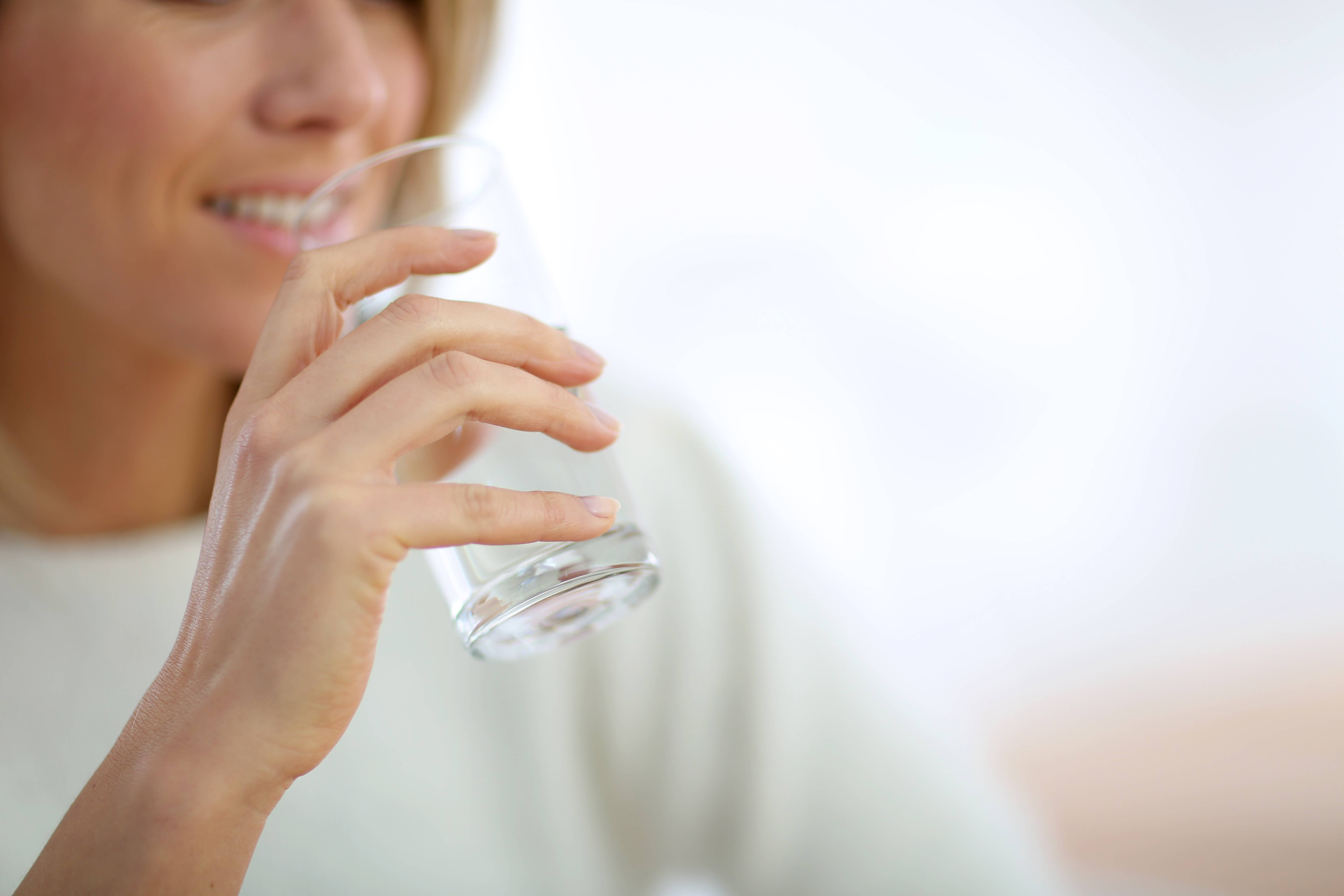 Closeup on glass of water held by woman's hand