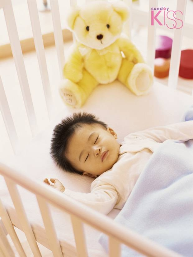high angle view of a baby boy sleeping in a crib