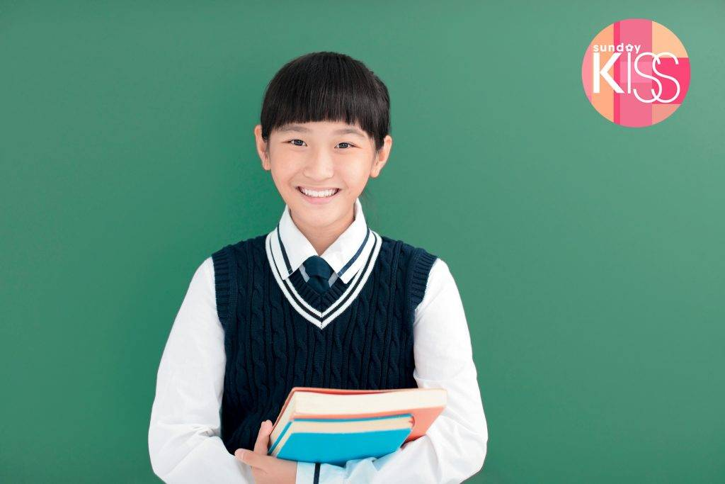smiling teenager Student girl  stand before chalkboard
