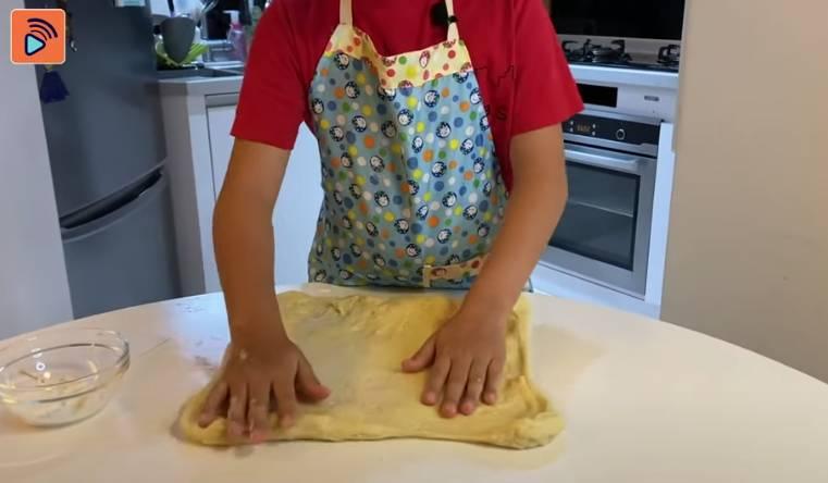 在枱上撒點麵粉,倒出麵糰,拉成正方形
