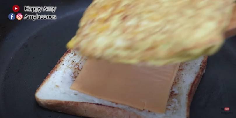 將兩片方包放上煎pan,依次序放上芝士、蛋餅、茄汁、火腿、醃青瓜、淨餘椰菜絲、另一片方包。