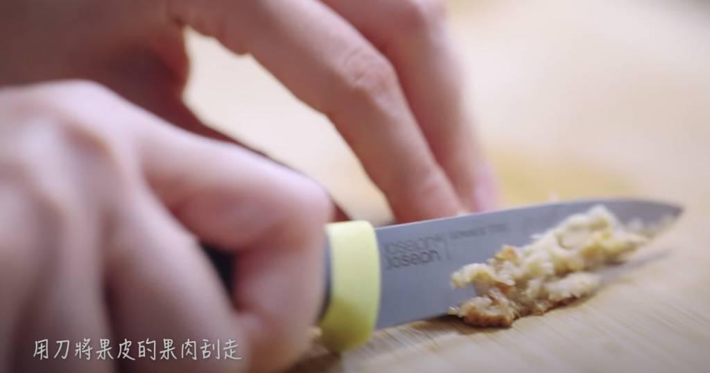 用刀將果皮的果肉刮走。