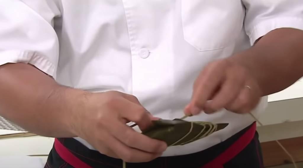 鹼水粽包成長方枕頭形,再用水草紮住。在枱角拍打糭,拍勻糭內糯米。