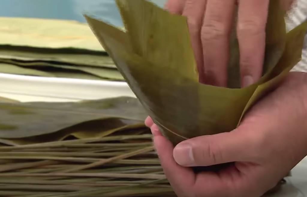 用兩片竹葉對角摺成三角錐形,放入40克糯米,加入20克開邊綠豆、鹹蛋黃及豬肉。