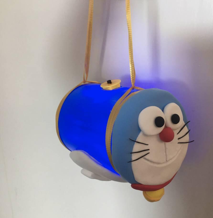 將藍色輕黏土加入少許白色成為淺藍色,並搓成圓形;用白色黏土分別搓成一個圓形(臉部)及2個圓形(眼白);黑色黏土搓出2個小圓形;及搓出6條鬚;用紅色黏土搓出小圓球(鼻子)及長條狀;用黃色搓成小圓球(鈴)。按圖示,將黏土拼出哆啦A夢的樣子,並輕輕在白色黏土上劃上嘴巴。(圖片來源:IG@toyisdream)